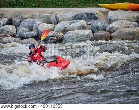 Fort Collins, CO, USA - May 7, 2021: Young male kayaker surfing a wave in the Poudre River Whitewater Park.