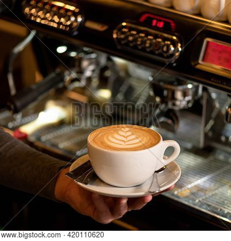 Barista Holding Cup Of Cappuccino Coffee Against Coffee Machine On Blurred Background. Cup Of Creamy