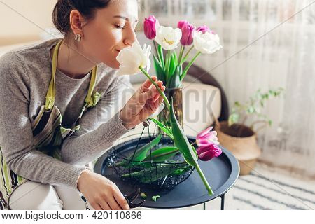 Woman Makes Flower Arrangement Of Tulips In Vase At Home. Florist Smells Blooms Picked Up In Basket.