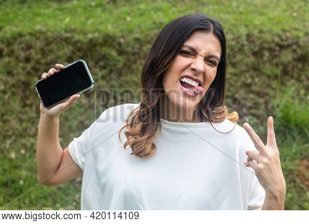 Latina Woman Showing Her Tongue And Gesturing Peace Sign, And Showing Her Phone In Park. Fresh Air