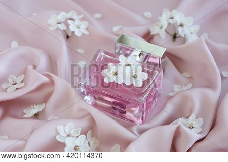 Close Up Glass Bottle Of Aromatic Luxury Perfume On Gentle Pink Silk Fabric With Sprig Blossom Flowe