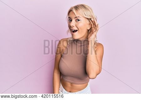 Young blonde girl wearing casual clothes smiling with hand over ear listening and hearing to rumor or gossip. deafness concept.