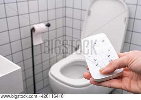 Remote Control With Buttons Of The Smart Toilet Bowl. High Technology Automatic Modern Flush Toilet