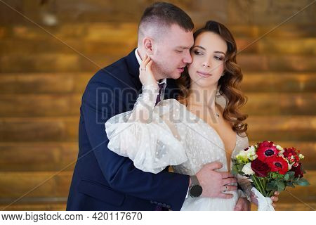 A Beautiful Newlyweds With A Bouquet. Bride Gently Strokes The Groom On The Face