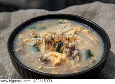 Close-up Of Pork Congee Or Chinese Rice Porridge With Minced Pork, Egg, Enoki Mushroom And Seaweed I