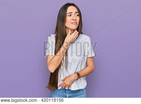Young hispanic girl wearing casual white t shirt touching painful neck, sore throat for flu, clod and infection