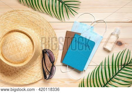 Straw Hat, Sunglasses, Two Passports And Medical Face Masks On A Wooden Surface. Concepts Of Protect