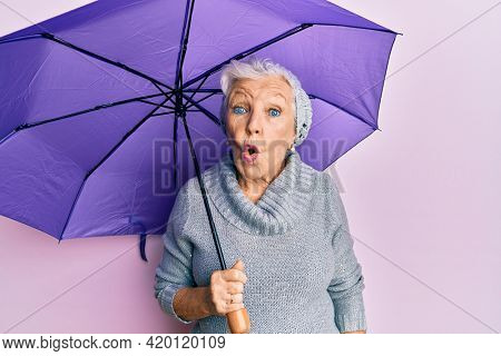 Senior grey-haired woman holding purple umbrella scared and amazed with open mouth for surprise, disbelief face