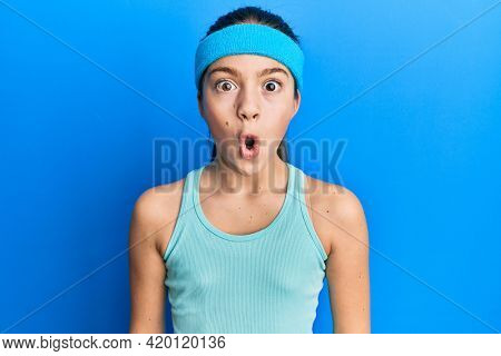 Beautiful brunette little girl wearing sportswear and diadem scared and amazed with open mouth for surprise, disbelief face