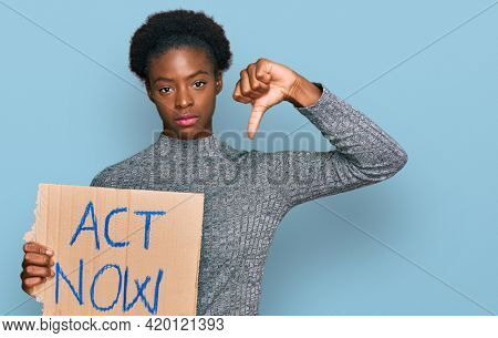 Young african american girl holding act now banner with angry face, negative sign showing dislike with thumbs down, rejection concept