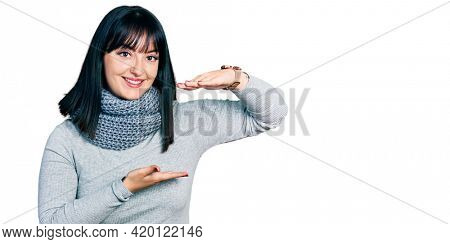 Young hispanic plus size woman wearing winter scarf gesturing with hands showing big and large size sign, measure symbol. smiling looking at the camera. measuring concept.