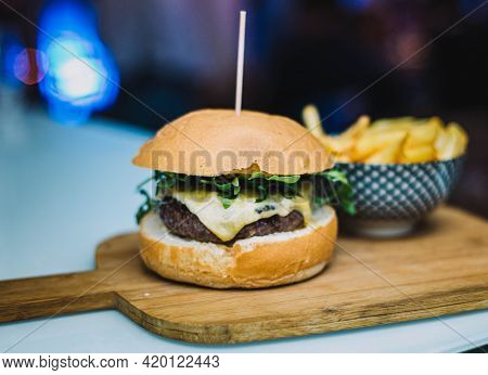 Gourmet Cheeseburger Served With Homemade Bread And Accompanied By French Fries