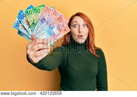 Beautiful redhead woman holding swiss franc banknotes scared and amazed with open mouth for surprise, disbelief face