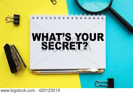 A Notepad With Text What's Your Secret On The Office Desk With Stationery. A Blank Notepad For Enter