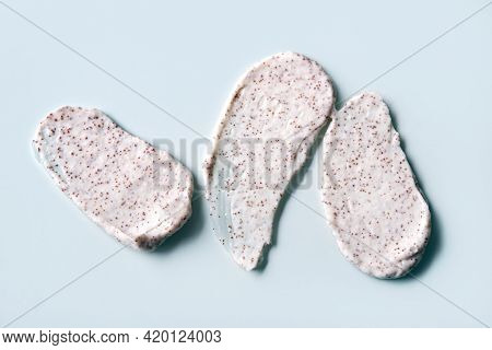 Smears Of Creamy Sorbet With Seeds Or Smears Of Coffee Scrub On Blue Background. Close-up