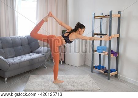 Young Woman Is Practicing Lord Of Dance Pose Natarajasana Doing Yoga At Home. Sport Fitness Training