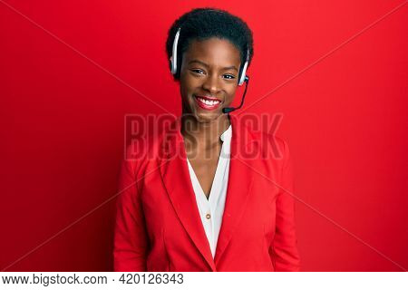 Young african american girl wearing call center agent headset looking positive and happy standing and smiling with a confident smile showing teeth