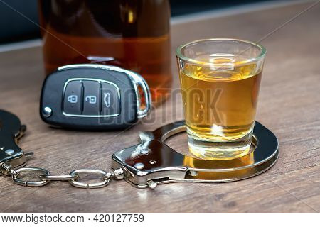 Close-up And Selective Focus Of Shot Of Whiskey In Handcuffs Against Background Of New Car Key And B