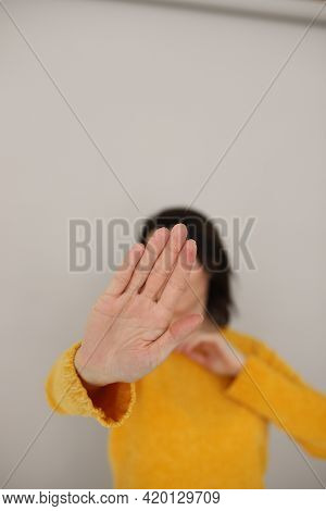 A Girl In A Yellow Sweater Of The Color Of The Year With Dark Hair Covers Her Face With An Outstretc