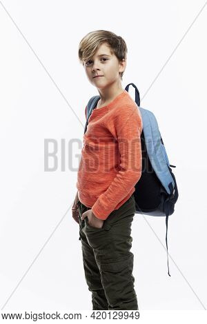 A 9-year-old Boy In An Orange Jacket And Jeans Stands Holding His Hands In His Pockets With A School