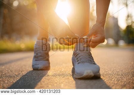 Running Woman Tying The Laces Of Sneakers Before Jogging On The Road In The Park In Sunny Weather, T