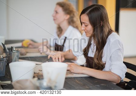 Two Women In Aprons Sitting By Table, Kneading Clay And Making Earthenware At Lesson