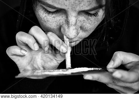 Drug Addict Sniffing And Snorting Cocaine,speed, Heroin Or Other Drug With Money Rolled Up On Mirror