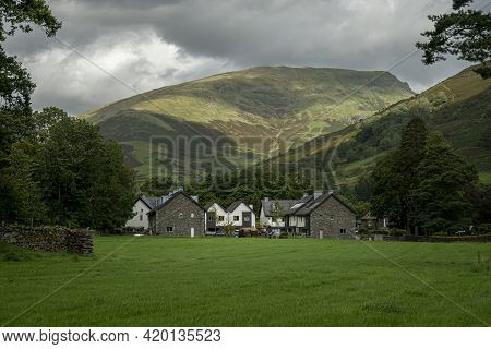 View Of Grasmere Village With Mountains In The Background, In The Lake District, Cumbria, Uk