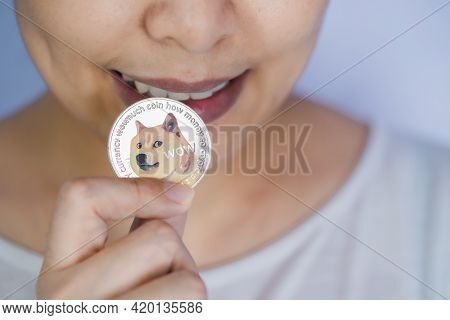 Dogecoin Doge Included With Cryptocurrency On Hand Working Asian Women Holding Coin In Front Face An