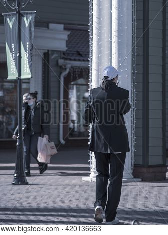 Russia, Vnukovo Outlet, March 2021. Tinted Monochrome Photo. A Woman In A Black Men's Suit And White