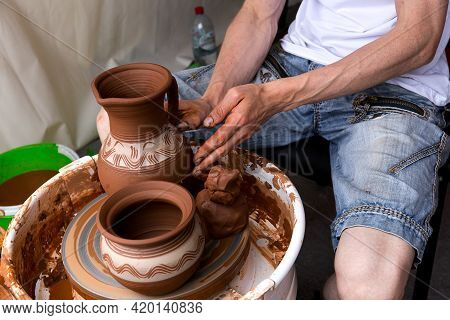 A Man Creates Pottery On A Potter's Wheel. Close-up Of The Potter's Hand.