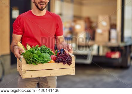Male Courier In Uniform Holding Grocery Box With Fresh Vegetables For Delivering While Standing Agai