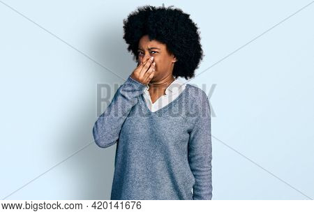 Young african american woman wearing business clothes smelling something stinky and disgusting, intolerable smell, holding breath with fingers on nose. bad smell