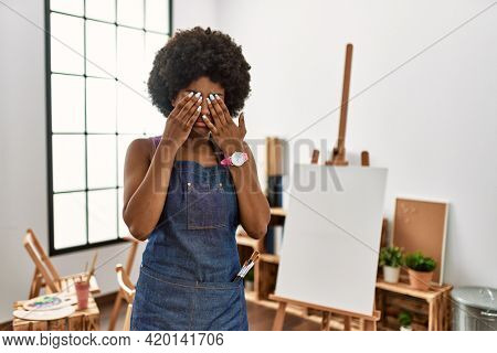Young african american woman with afro hair at art studio rubbing eyes for fatigue and headache, sleepy and tired expression. vision problem