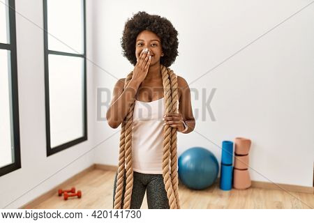 Young african american woman with afro hair at the gym training with battle ropes laughing and embarrassed giggle covering mouth with hands, gossip and scandal concept
