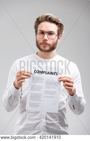 Dissatisfied Young Man Wearing Glasses Standing Holding Up A List Of Complaints With A Serious Inten