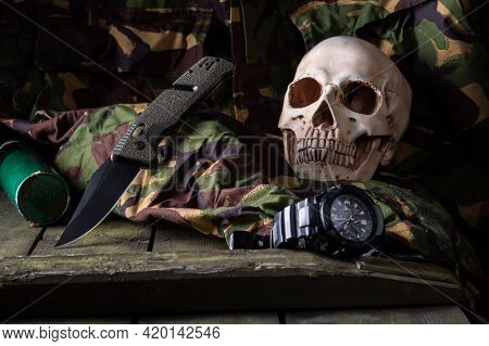 A Knife On A Military Uniform With A Human Skull. Military Knife And Military Grenade.