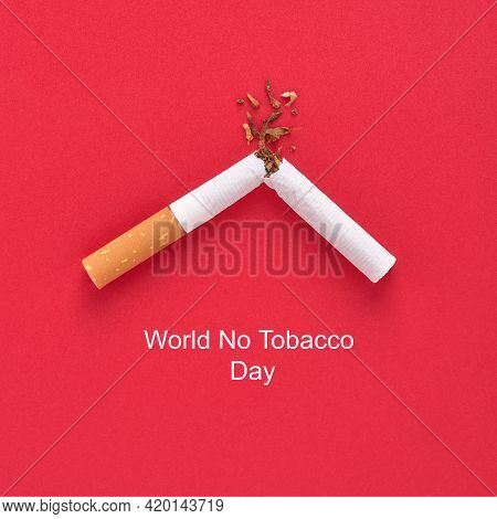 A Broken Cigarette With Tobacco And Inscription World No Tobacco Day On Red Background.