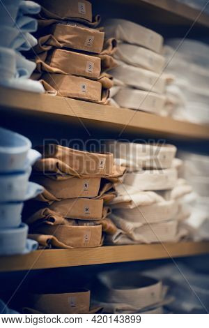 A Stack Of Folded Shirts. Stacks Of Clothes. Shopping In Store. Clothing On The Shelves In Shop For