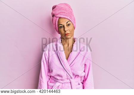 Middle age hispanic woman wearing shower towel cap and bathrobe relaxed with serious expression on face. simple and natural looking at the camera.