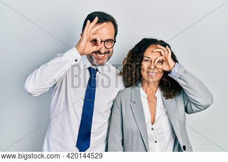 Middle age couple of hispanic woman and man wearing business office uniform doing ok gesture with hand smiling, eye looking through fingers with happy face.