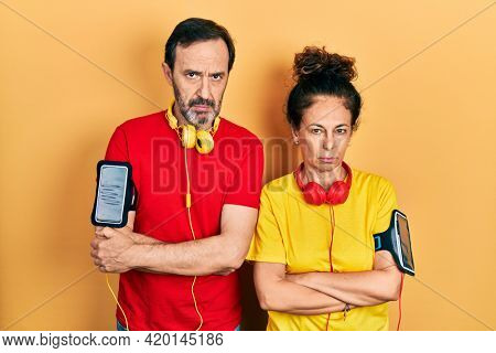 Middle age couple of hispanic woman and man wearing sportswear and arm band skeptic and nervous, disapproving expression on face with crossed arms. negative person.