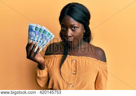 African young woman holding south african 100 rand banknotes scared and amazed with open mouth for surprise, disbelief face