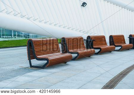 Recreation Area With Empty Contemporary Wooden Benches Along White Curved Wall Near Modern Business
