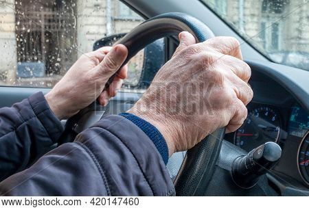 Close-up Of The Hand Of An Adult Man In A Passenger Car, Holding The Steering Wheel In Cold Rainy We