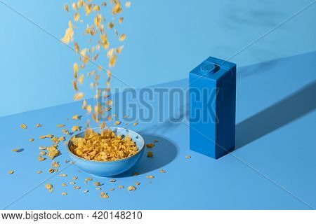 Pouring Cereals In A Bowl On A Blue Colored Table. Breakfast Table With Cornflakes Cereals In A Bowl