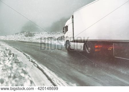 White Modern Truck Moving Fast In Winter On A Road With Snow