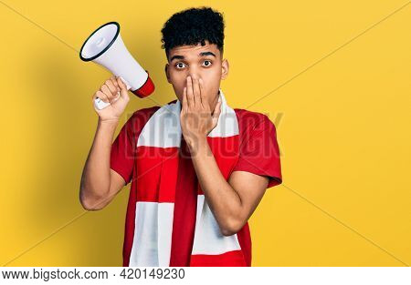 Young african american man football hooligan holding megaphone covering mouth with hand, shocked and afraid for mistake. surprised expression