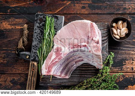 Raw Rack Of Pork Loin Chops With Ribs On A Butcher Board With Meat Cleaver. Dark Wooden Background.