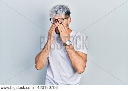 Young hispanic man with modern dyed hair wearing white t shirt and glasses rubbing eyes for fatigue and headache, sleepy and tired expression. vision problem